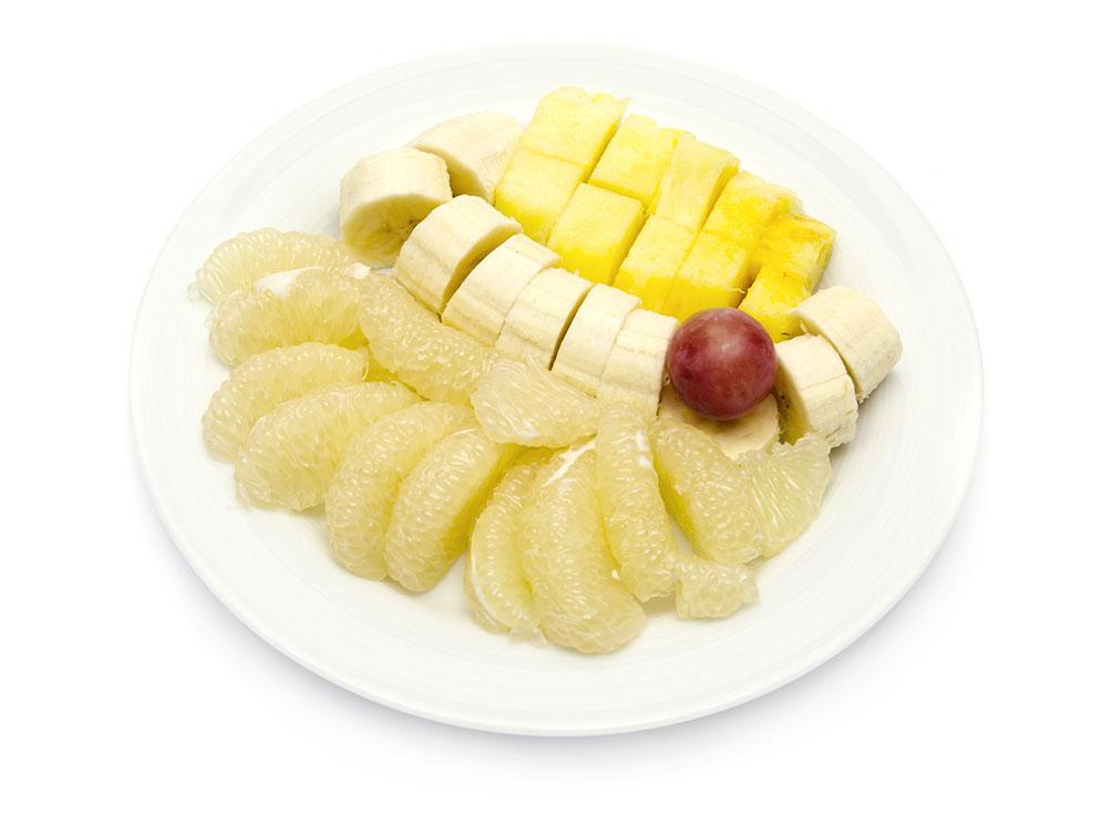 Obstteller mit Ananas, Banane, Sweetie und Weintraube