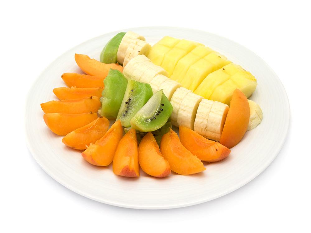 Obstteller: Ananas, Banane, Aprikose und Kiwi